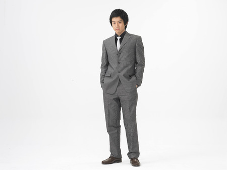 Asian business man stuffing hands into his pockets isolated on white