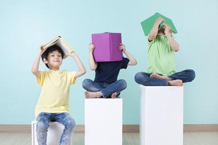 Asian cute children reading books on chair