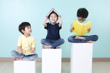 Aziatische schattige kinderen lezen boek op stoel Stockfoto