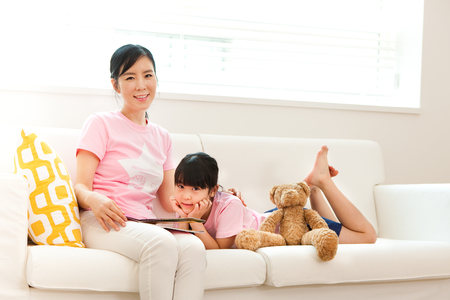 Asian mother and daughter reading book together on sofa