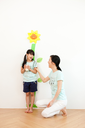 Asian mother and daughter measure their height indoor