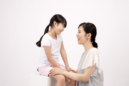 Asian mother and daughter having fun with smile isolated on white 版權商用圖片