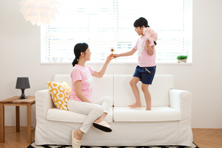 Asian mother and daughter have a good time on sofa indoor