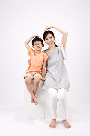 Asian mother and son make heart shape with their arms isolated on white