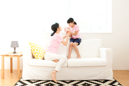 Asian mother and daughter having fun on sofa indoor