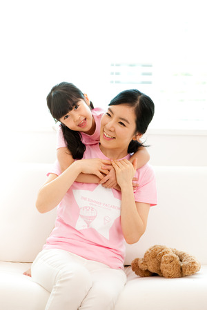 Asian mother and daughter hug each other on sofa