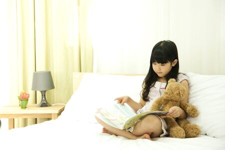 Asian cute girl reading book with teddy bear on bedroom