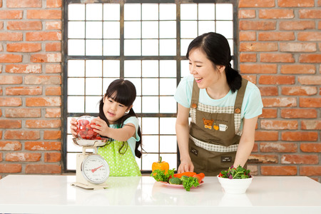 Asian mother and daughter weigh vegetable Stok Fotoğraf