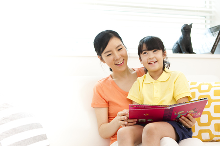 Asian mother and daughter reading book in living room Stock Photo
