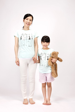 Asian mother and daughter with teddy bear isolated on white Stock Photo