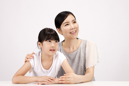 Asian mother and daughter looking at something isolated on white Stock Photo