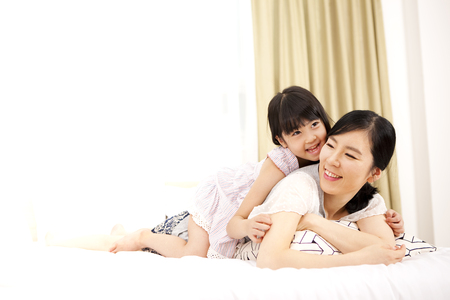 Asian mother and daughter lying on bedroom with smile