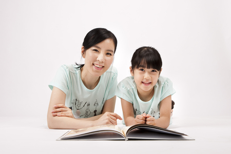 Asian mother and daughter reading book together isolated on white Stock Photo