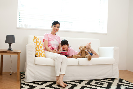 Asian mother and daughter reading book together on sofa indoor Stock Photo