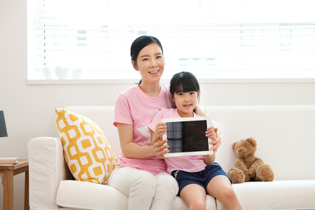 Asian mother and daughter using tablet pc on sofa indoor