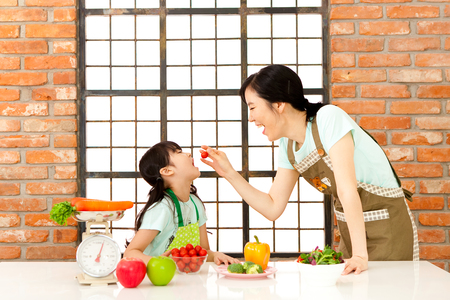 Asian mother and daughter eating vegetable