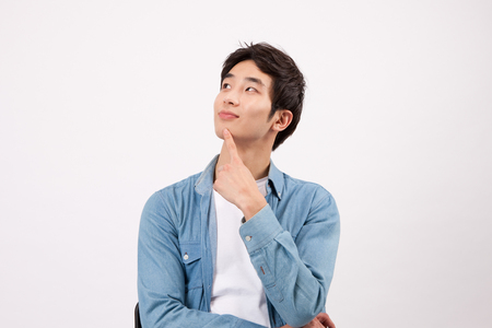 Asian young man thinking something isolated on white Stock Photo