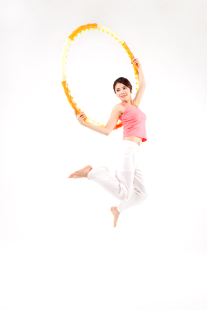Asian attractive young woman jumping with hula hoop isolated on white Stock Photo
