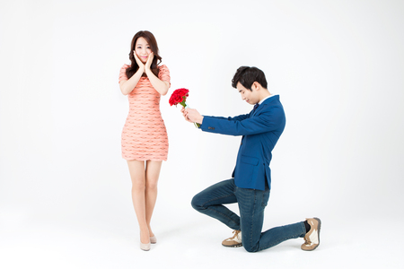 Portrait of Asian handsome man kneeling down and giving bouquet for propose isolated on white