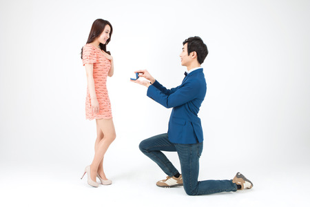Portrait of Asian handsome man kneeling down and giving a ring for propose isolated on white