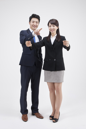Portrait of Asian business couple holding something together isolated on white