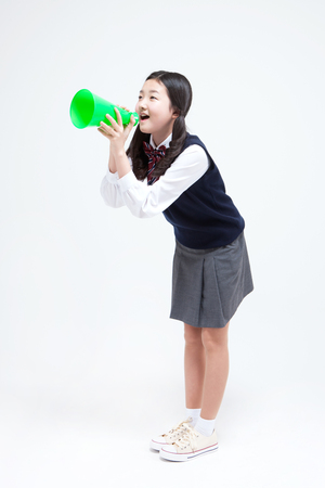 loudspeaker: Asian middle school girl with loudspeaker isolated on white Stock Photo
