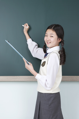 Asian middle school girl writing on the blackboard isolated on white