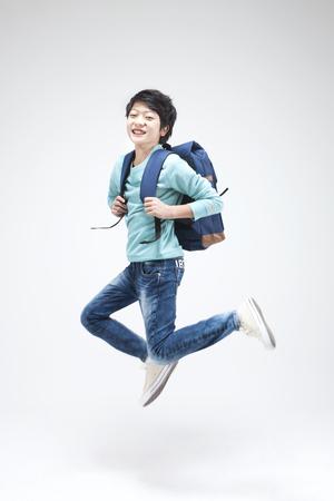 아시아 십대 소년 흰색으로 격리 학교 가방과 함께 점프 스톡 콘텐츠