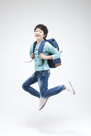 Asian teenager boy jumping with school bag isolated on white