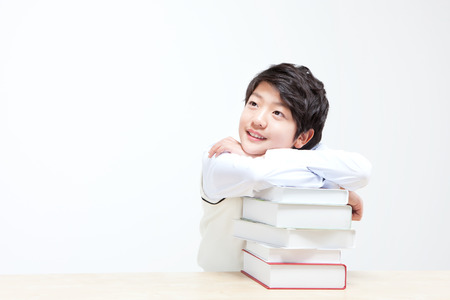 Asian middle school boy thinking something with books isolated on white
