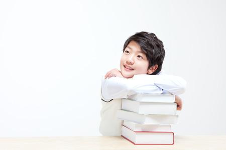Garçon asiatique moyen penser quelque chose avec des livres isolés sur blanc Banque d'images - 87476001