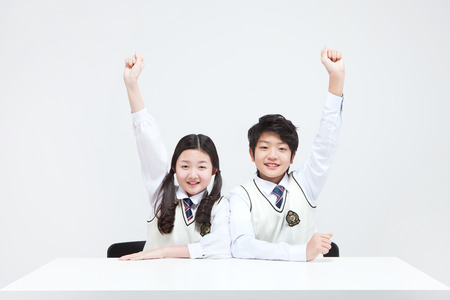 Asian middle school boy and girl answering the question isolated on white