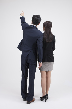 Portrait of rear view Asian business couple pointing together isolated on white