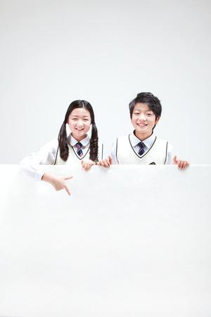 아시아 중학생 소년과 소녀 화이트 절연 큰 화이트 보드 뒤에 초상화