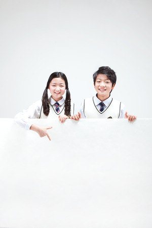 Portrait of Asian middle school boy and girl behind big white board isolated on white