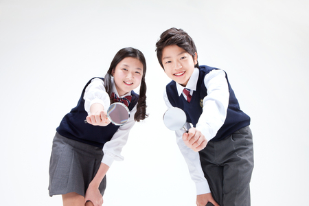 Portrait of Asian middle school boy and girl using magnifier isolated on white