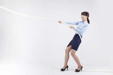 白で隔離ロープを引っ張るアジア ビジネス ・ ウーマンの肖像画