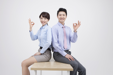 Portrait of Asian business couple in okay gesture isolated on white