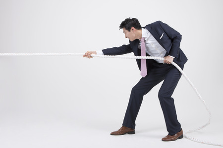 Portret van de Aziatische bedrijfsmens die een kabel trekt die op wit wordt geïsoleerd