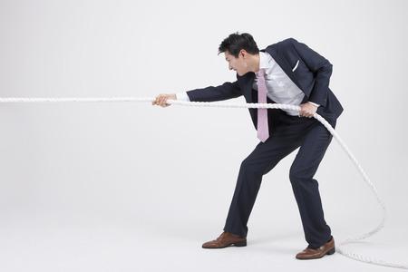 Ritratto dell'uomo asiatico di affari che tira una corda isolata su bianco Archivio Fotografico - 87067439