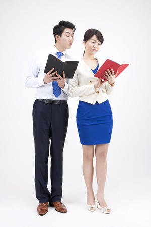 Portrait of Asian business couple reading notebook isolated on white Stock Photo