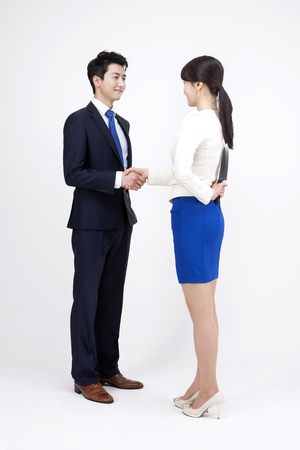 two faced: Portrait of Asian two-faced business couple shaking hands isolated on white