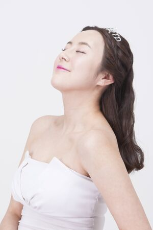 Portrait of Asian beautiful woman in tiara while closing her eyes isolated on white