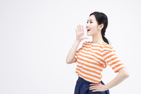 Portrait of side view Asian woman calling somebody while smiling isolated on white Banco de Imagens