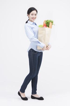 화이트 절연 음식과 종이 가방을 들고 아시아 아름 다운 여자의 초상화
