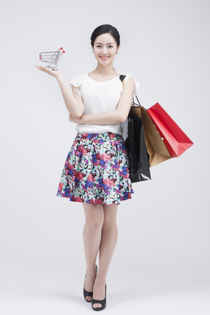 Portrait of Asian woman holding small shopping cart with lots shopping bags isolated on white