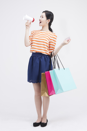 loudspeaker: Portrait of Asian woman with credit card,  loudspeaker,  lots shopping bags isolated on white Stock Photo