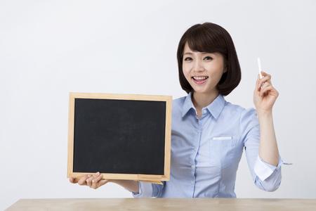 Portret van Aziatische vrouwelijke leraar met klein bord op het bureau dat op wit wordt geïsoleerd