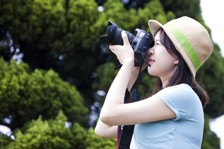 Portrait of Asian beautiful woman in hat taking picture outdoor
