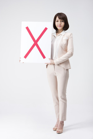 Portrait of Asian business woman holding wrong sign board isolated on white Stock Photo